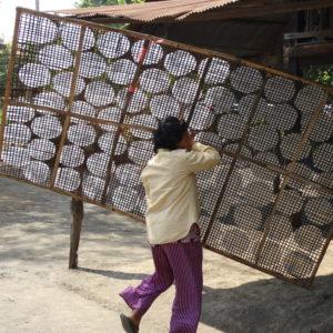 Séchage des feuilles de riz au soleil sur une claie en bambou